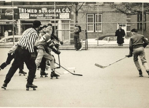 Paul Chapey is to the immediate right of the referee. Chapey is the founder of the Hosers and his roller hockey roots is the Fort Fort Hamilton Roller Hockey League in Brooklyn, circa 1970? New York City is where most people believe roller hockey began in the USA